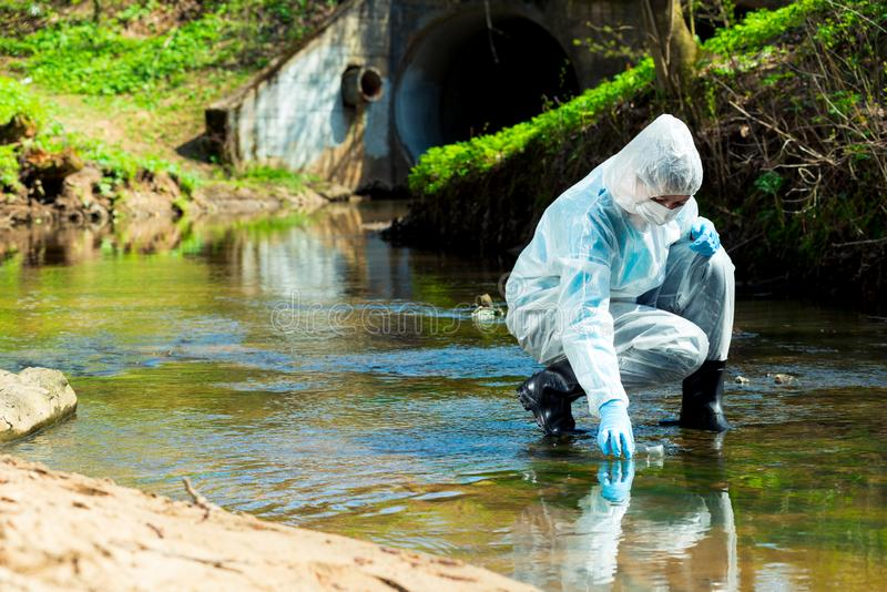 Ecological disaster, contaminated water comes out of the sewage system - an ecologist takes a sample of water. For research royalty free stock images