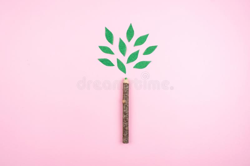 Ecological friendly, sustainable environment, Eco conscious concept with pen in the form of a tree trunk with green leaves on pink royalty free stock photos