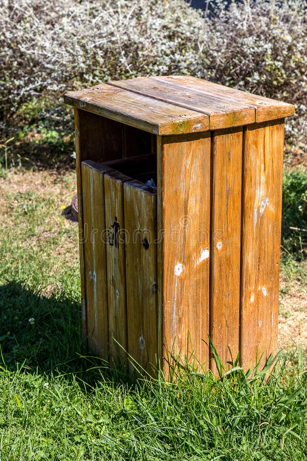 Ecological Trash Bin. Wooden ecological trash bin on a park stock photo