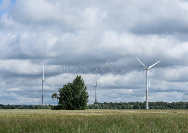 Ecologieconcept: Blauwe hemel, witte wolken en windturbine Windgenerator voor elektriciteit, alternatieve energiebron stock afbeelding