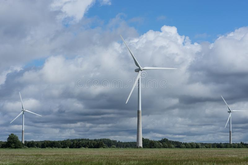 Ecologieconcept: Blauwe hemel, witte wolken, windturbine en gewassengebied Windgenerator voor elektriciteit, alternatieve energie royalty-vrije stock fotografie