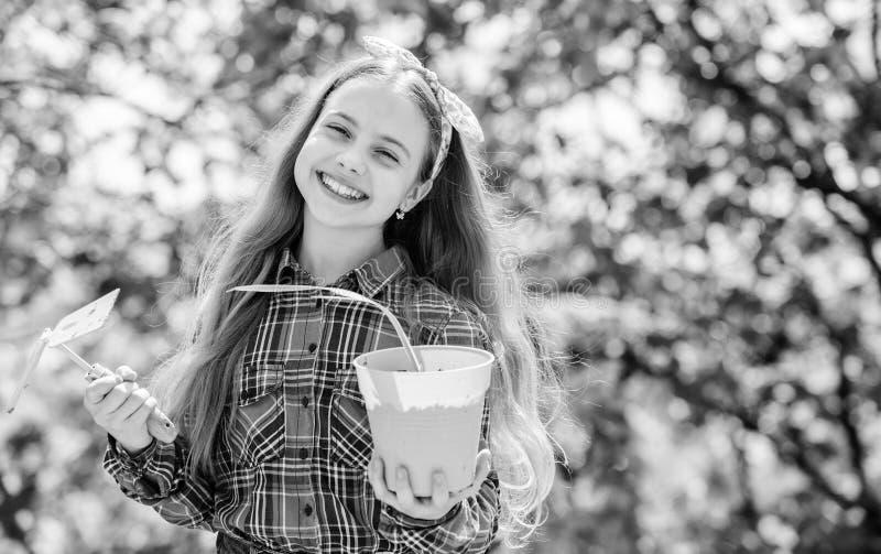 ecologiemilieu De Dag van gelukkige Kinderen meisje met het tuinieren hulpmiddelen De Dag van de aarde meisjejong geitje in de bo stock afbeelding