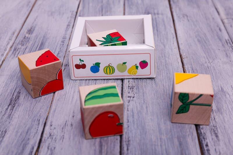 Ecologische houten kubussen met vruchten Kleurrijke geometrische cijfers aangaande de houten achtergrond stock afbeeldingen