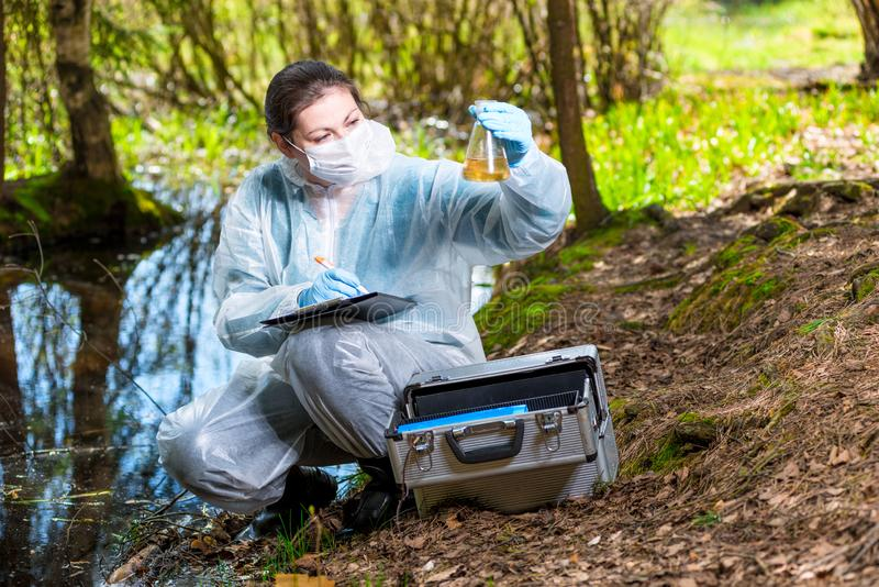 Ecologist biologist with a sample of water samples. From a forest lake stock photo