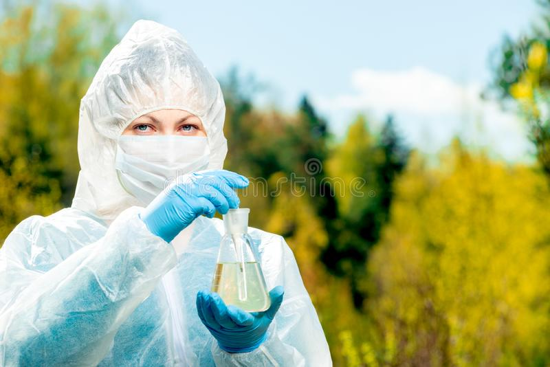 The ecologist carries out research of water in the lake with the help of tools, shooting in nature while stock photos