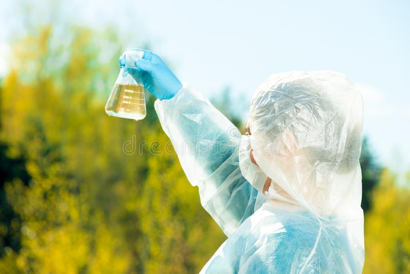 Ecologist determines the properties of water visually, the sample is taken in a flask. From the pond stock photos