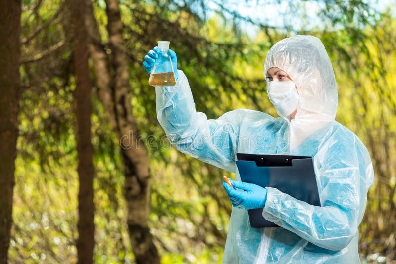Ecologist examines the dirty water. In the flask royalty free stock image