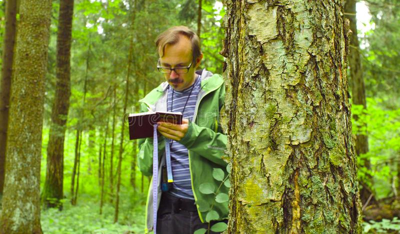 The ecologist in a forest writing in notebook. stock photo