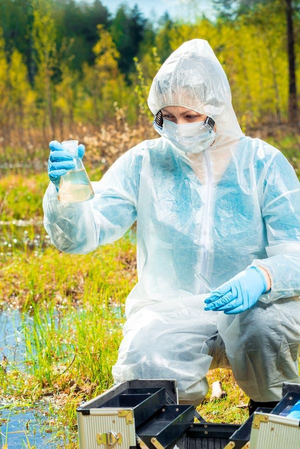 Ecologist met hulpmiddelen en flessen die watersteekproeven van een bosmeer voor onderzoek nemen stock foto's