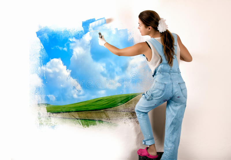 Ecologist Mural Painting on Wall. Young woman painting a nature landscape on wall with roller. Mural painting on wall. Ecologist royalty free stock photo