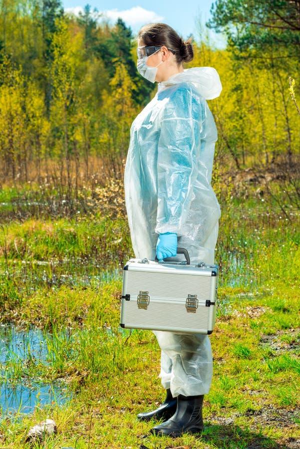 ecologist in overall op het meer met materiaal om water te nemen stock afbeelding