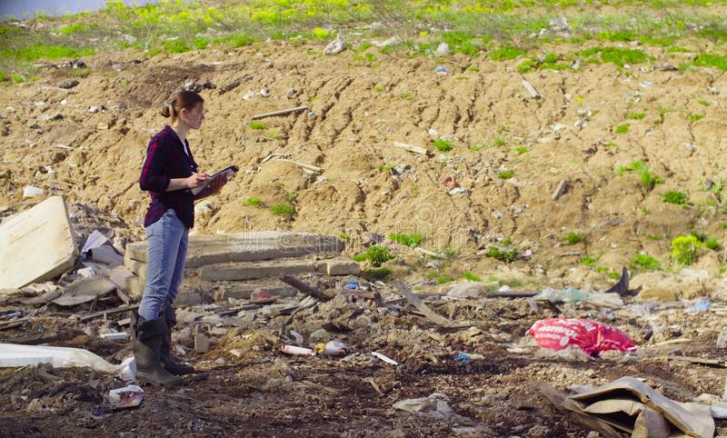 Ecologist during the research on garbage dump. Woman ecologist during the research on garbage dump. She writing something on the sheets of paper royalty free stock photo