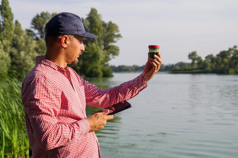 Ecologist on river bank examines container with green algae and holds tablet. Research of ecological problems. environment, nature, save earth stock images
