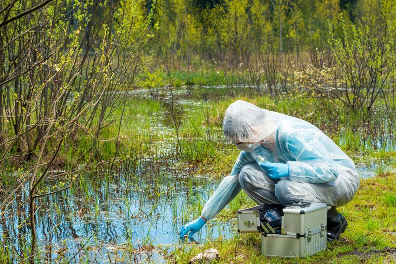The ecologist takes a sample of water from a forest reservoir. In protective clothing stock photos