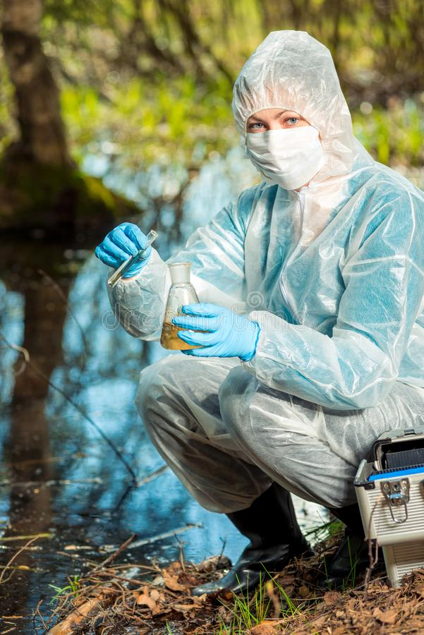 Ecologist and with test tubes and flasks analyzes water. In a forest pond royalty free stock photography