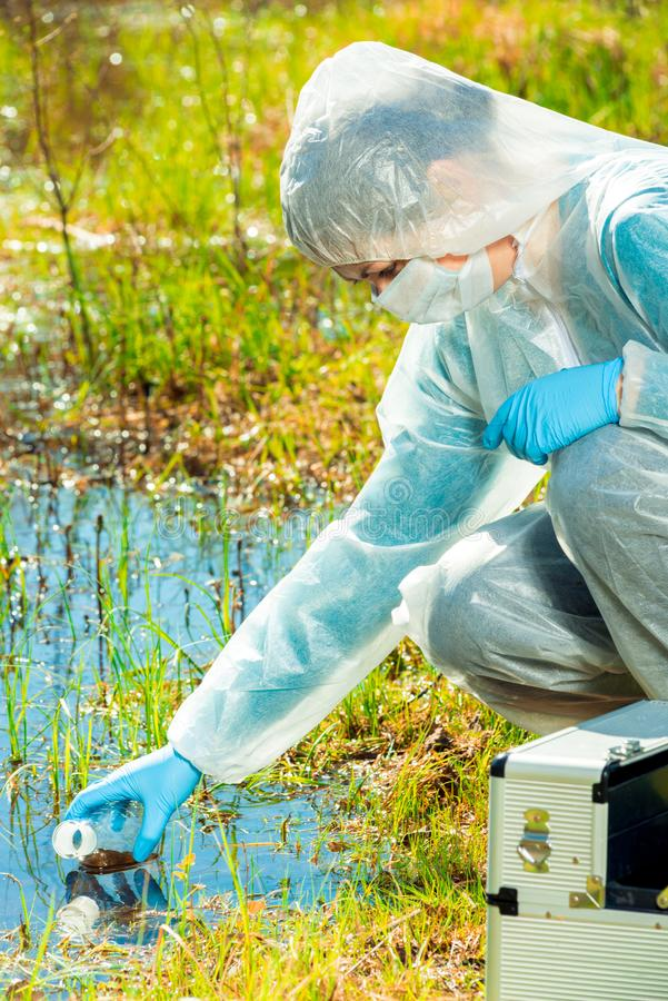 Ecologist woman in protective clothing takes samples of forest lake royalty free stock photo