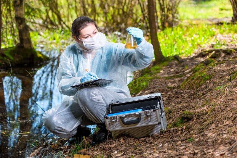 ecologistbioloog met een steekproef van watersteekproeven stock foto