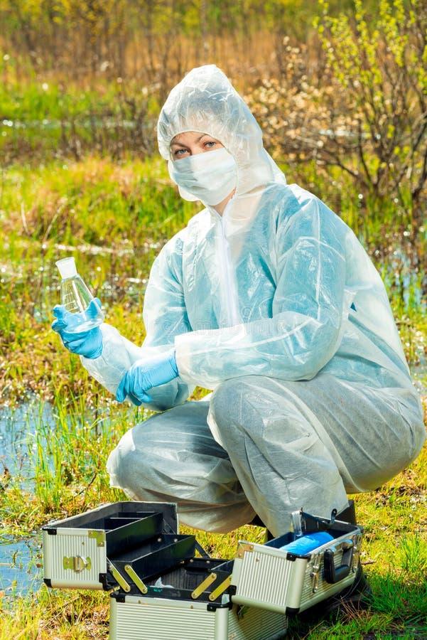 Ecologistvrouw in beschermende kleding met een fles voor een watertest stock fotografie