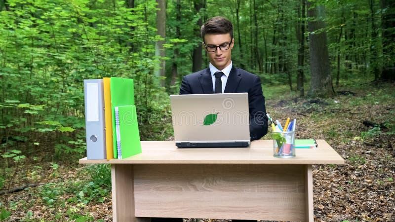 Ecologo che crea progetto di risparmio di eco, sedentesi nella foresta, concetto di disboscamento fotografie stock