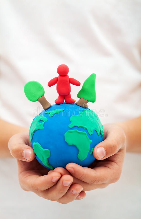 Ecology concept with clay world globe in child hand. Ecology concept - child hands holding clay world globe with trees and people stock photography