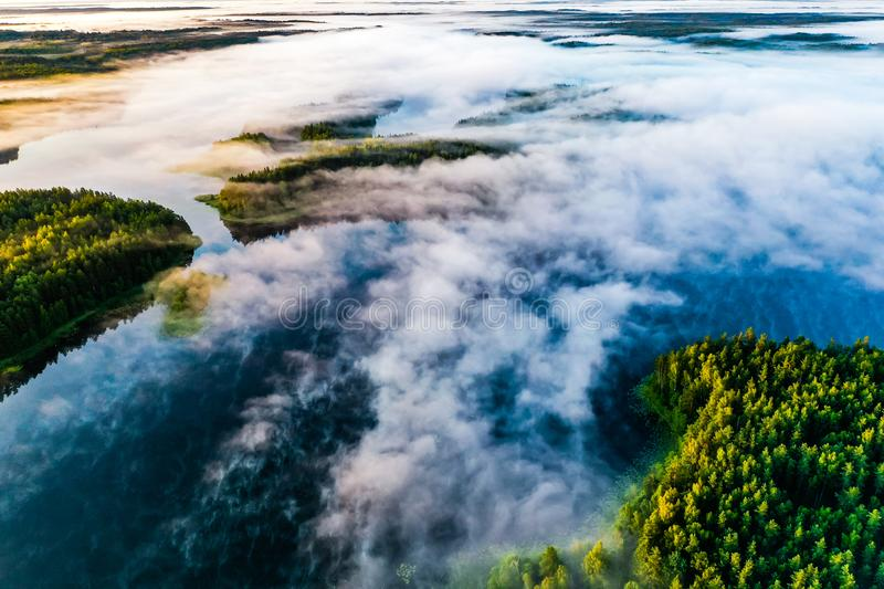 Ecology concept. Thick fog over blue lakes at dawn. Aerial landscape stock photo