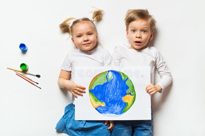 Ecology concept with two prety little kids painting sad earth on white background. Copy space, top view stock photography