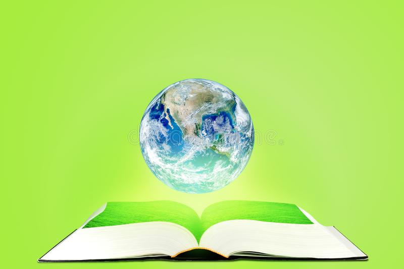 Planet earth globe floating over opened book with green background. Elements of this image furnished by NASA. royalty free stock photography