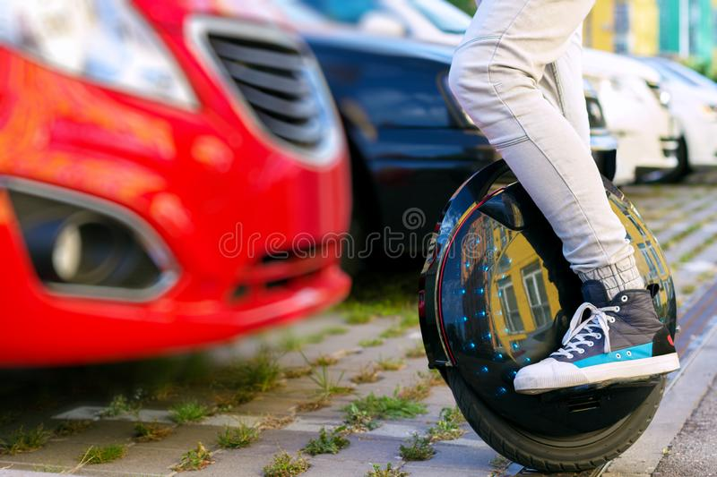 Ecology electric transport balancing unicycle compare diesel fuel car. Future is now concept. Ecological transport. Black modern futuristic electric unicycle royalty free stock photography