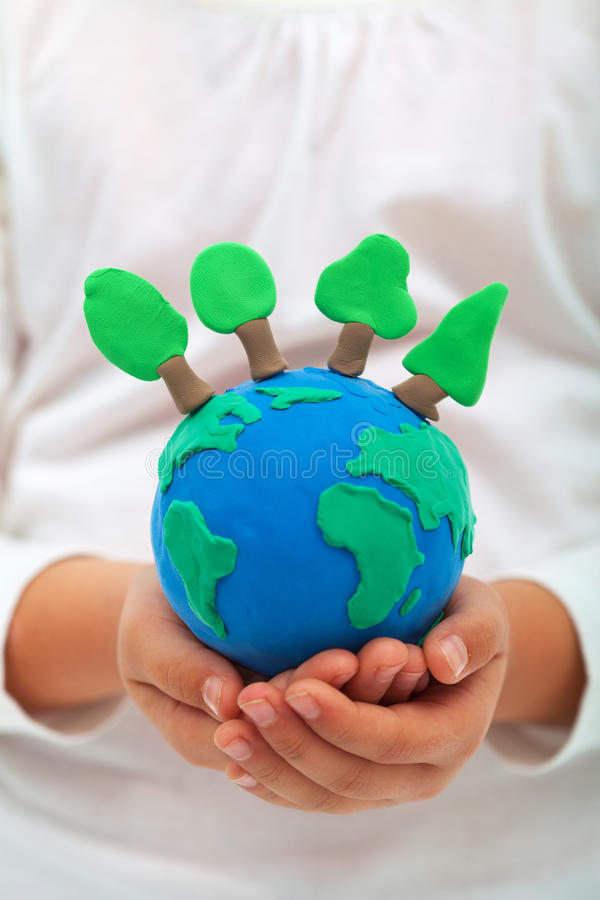 Ecology and environment concept with trees on clay world. In child hands royalty free stock photos