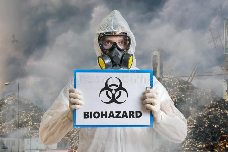 Ecology and pollution concept. Man in coveralls is warning against biohazard waste stock photos