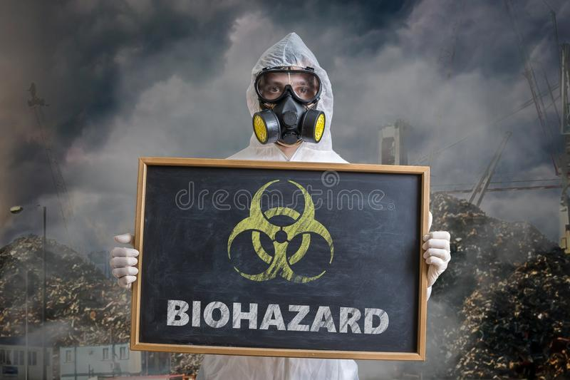 Ecology and pollution concept. Man in coveralls is warning against biohazard waste.  royalty free stock image
