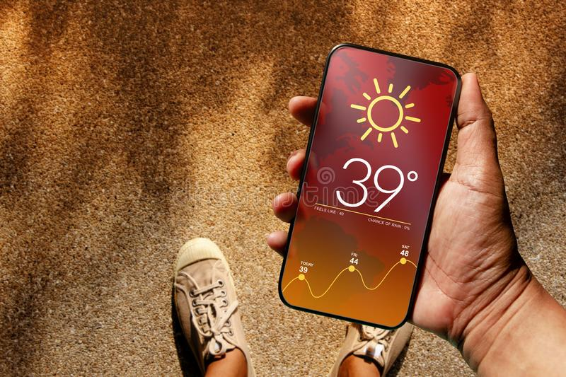Ecology and Technology Concept. High Temperature Weather show on Mobile Screen on Hot Sunny Day. Top View, Grunge Dirty Concrete stock images