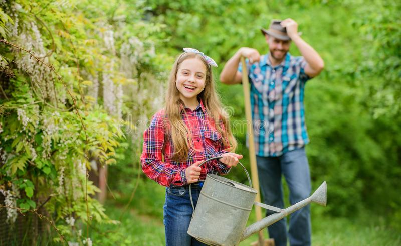 Ecology. Watering can and shovel. spring village country. family farm. little girl and happy man dad. earth day. father. Ecology. Watering can and shovel. spring royalty free stock images