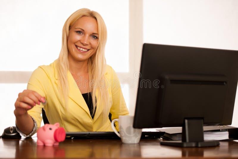 Economia do negócio - a mulher põe uma moeda no piggybank no escritório imagens de stock royalty free