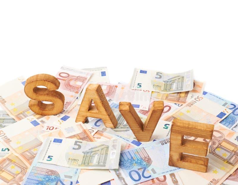 Economias da palavra sobre a pilha de dinheiro fotografia de stock