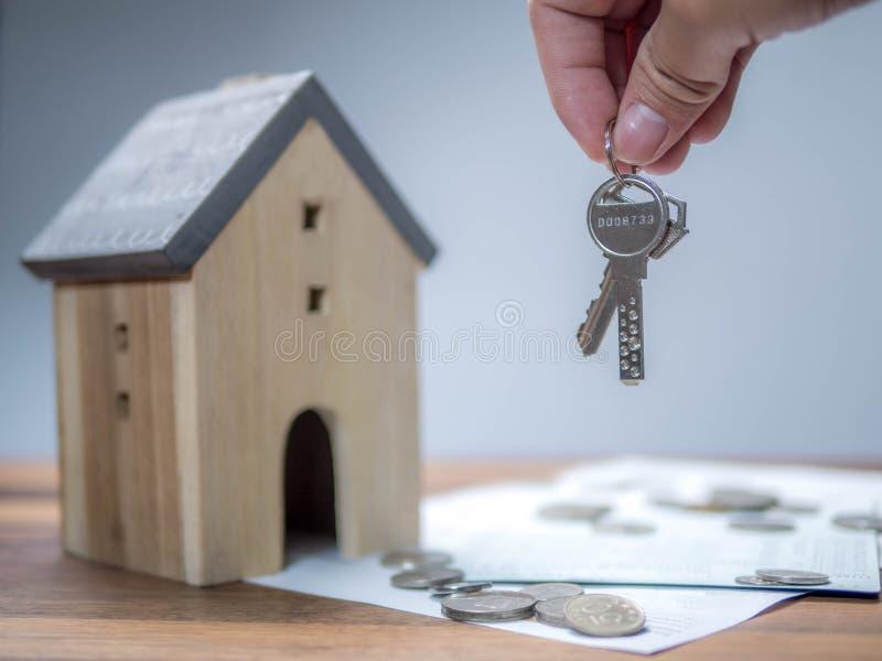 Economias do agregado familiar e finanças, mão que guarda a chave com modelo da casa Conceito de salvamento do dinheiro, bens imo fotografia de stock