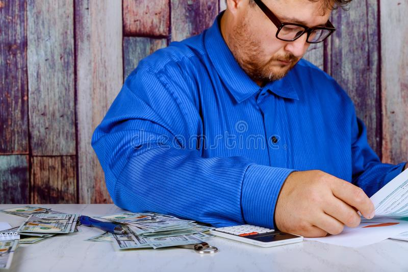 economias, finanças, economia e fim home do conceito acima do homem com a calculadora que conta o dinheiro e que faz anotações em fotos de stock royalty free