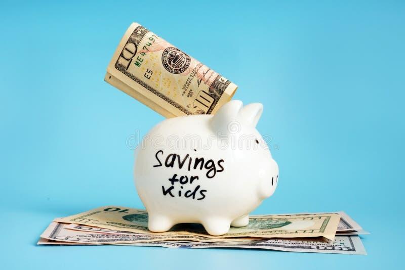 Economias para as crianças escritas em um mealheiro fotos de stock royalty free