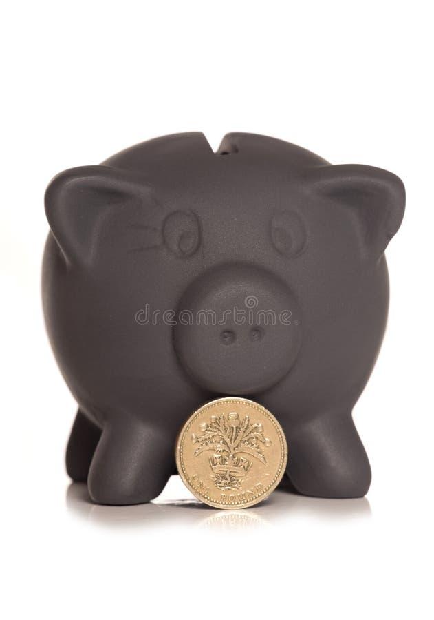 Economias pretas mealheiro de sexta-feira e moeda de libra imagem de stock royalty free