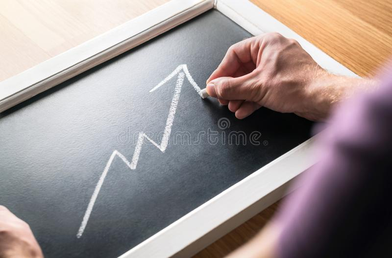 Economic growth. Forecast of growing revenue or profit in economy. Report of finances. Successful business man drawing increasing. stock photos