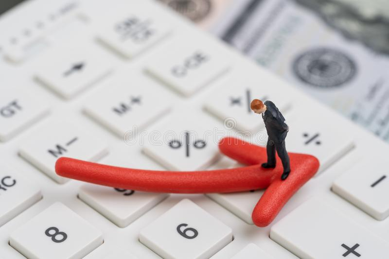 Economic recession, bear stock market or financial crisis concept, miniature businessman standing on red pointing down arrow on. White calculator with stock photos