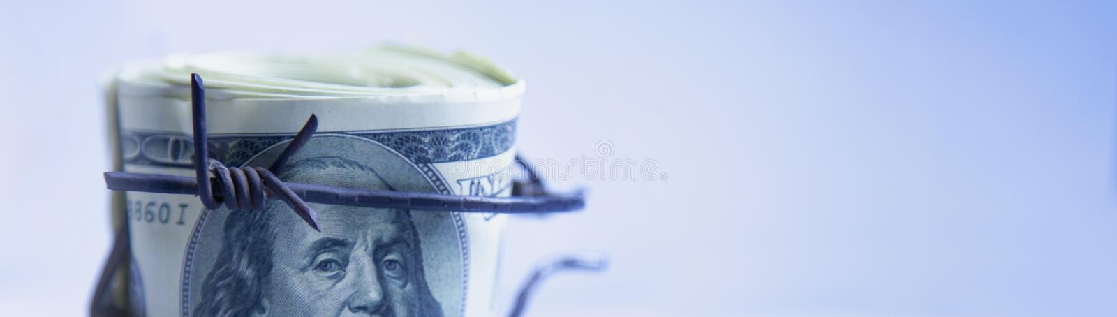 Economic warfare, sanctions and embargo busting concept. US Doll. Ar money wrapped in barbed wire stock image