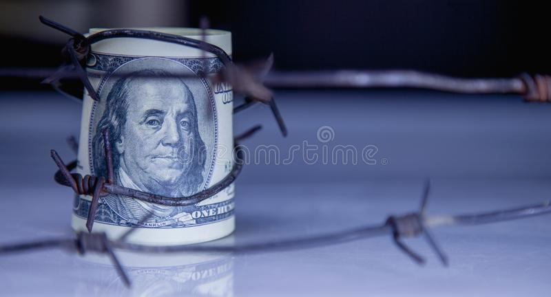 Economic warfare, sanctions and embargo busting concept. US Doll. Ar money wrapped in barbed wire royalty free stock photo