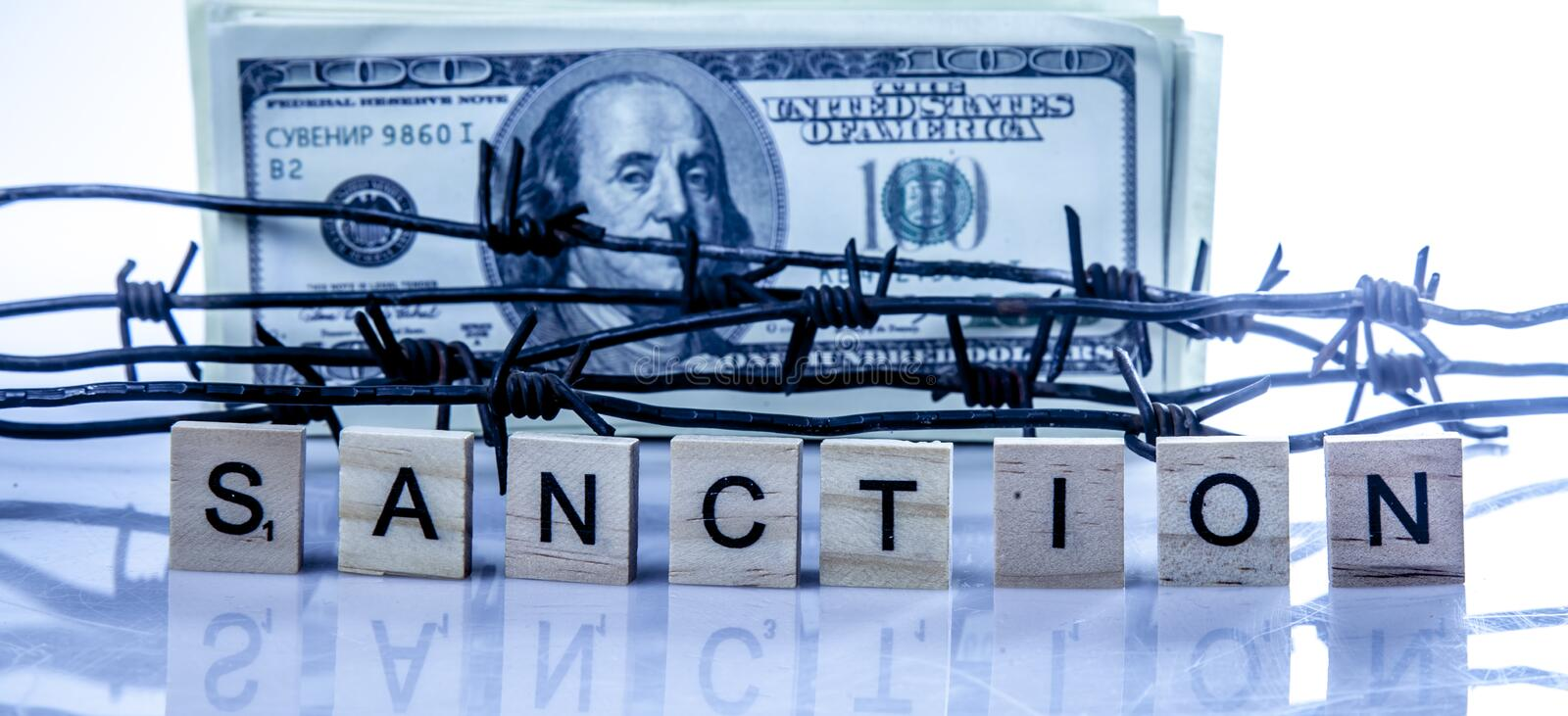 Economic warfare, sanctions and embargo busting concept. US Dollar money wrapped in barbed wire.  royalty free stock photography