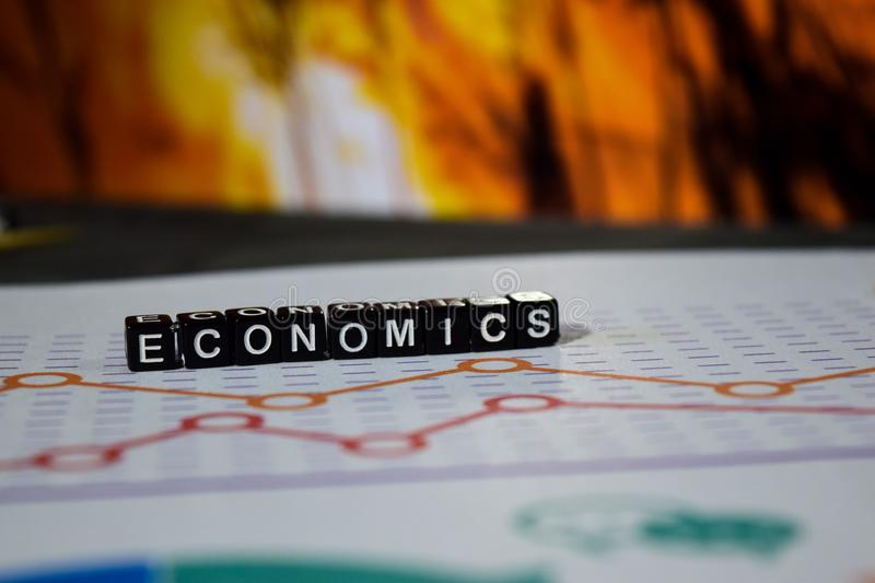 Economics on wooden blocks. Investment Income Profit Revenue Savings Concept stock photos