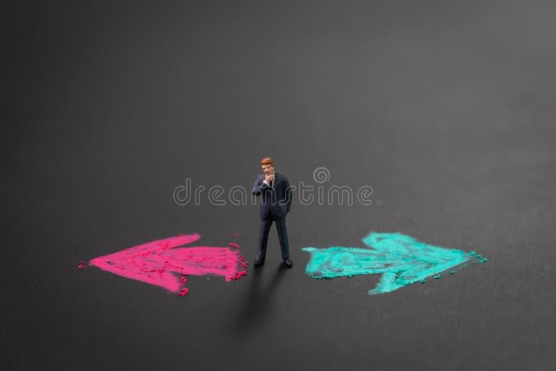 Economisch besluit, carrière of kansoptie in het leven om concept te kiezen, miniatuurzakenman die in het midden van linker denke royalty-vrije stock afbeeldingen