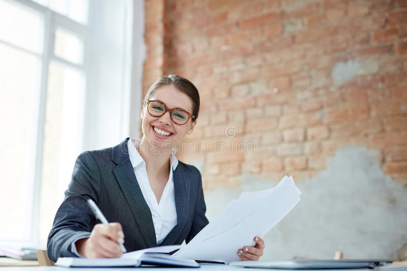 Economist in office. Successful financier with papers making notes in notebook in office royalty free stock image