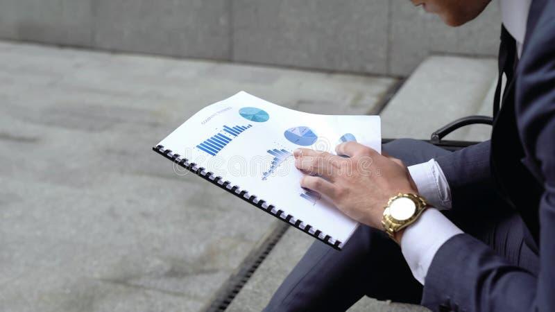 Economista che analizza i grafici ed i grafici prima della riunione importante, confrontante i dati fotografia stock libera da diritti