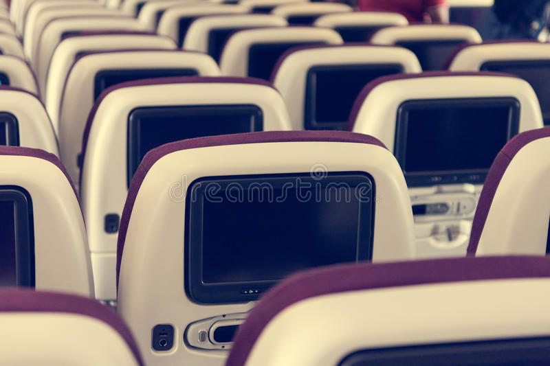 Economy class airplane interior. LCD displays on the rear side of seats royalty free stock image