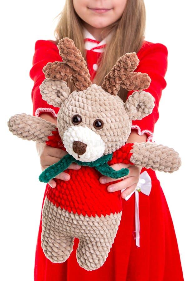 Ecospeelgoed, het herten zachte stuk speelgoed in de handen van Kerstmismeisjes op de witte achtergrond stock afbeeldingen